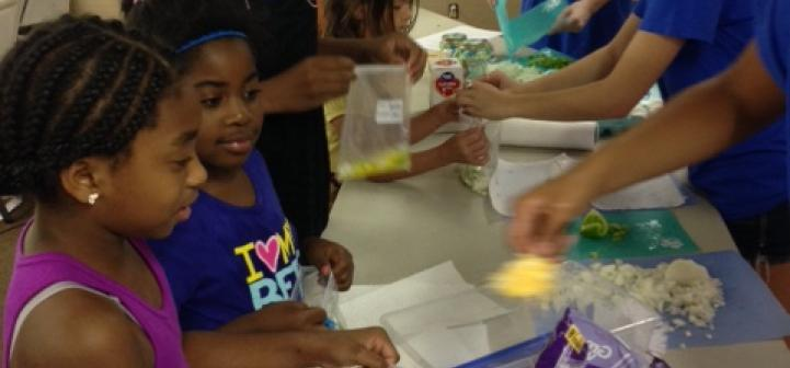 Children making a healthy recipe during a summer camp.